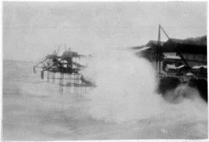 Waves washing over the loading piers on 1 Jan 1932